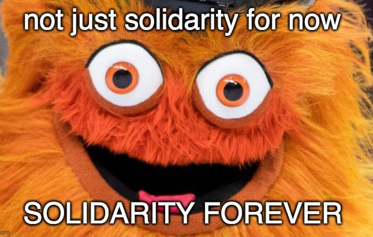 "A close-up picture of Gritty, the NHL Flyers mascot, with the words ""Not Just Solidarity For Now, Solidarity Forever"" written on the picture"