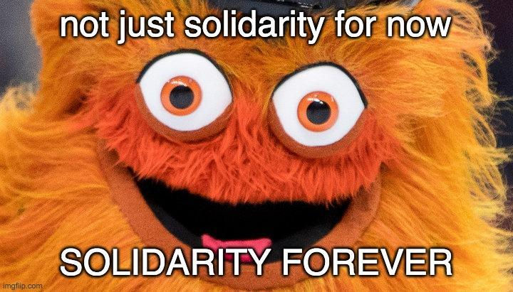 """A close-up picture of Gritty, the NHL Flyers mascot, with the words """"Not Just Solidarity For Now, Solidarity Forever"""" written on the picture"""
